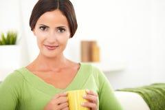Młoda kobieta trzyma kawowego kubek Obrazy Royalty Free
