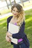 Młoda kobieta trzyma laptop outdoors Fotografia Stock
