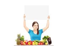 Młoda kobieta trzyma pustego panelu obsiadania na stole z f i Zdjęcia Royalty Free