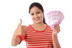 Młoda kobieta trzyma 500 rupii notatki i robi kciukowi up gestykuluje Obraz Stock