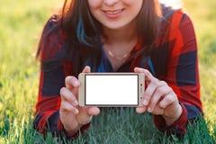 M?oda kobieta trzyma smartphone z pustym bielu ekranem przed ona z dwa r?kami Z miejscem minowa? przestrze? Outdoors, obrazy royalty free