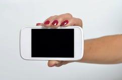 Młoda kobieta trzyma telefon komórkowego Obrazy Royalty Free