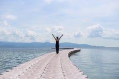 Młoda kobieta w czerni sukni na molu w morzu Fotografia Royalty Free