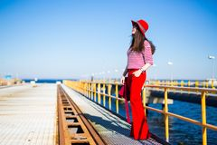 Młoda kobieta w czerwieni pozuje na molu Zdjęcia Stock