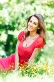Młoda kobieta w czerwieni sukni obsiadaniu na trawie Zdjęcie Royalty Free