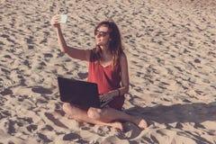 Młoda kobieta w czerwieni sukni z komputerem i smartphone na bea Fotografia Stock