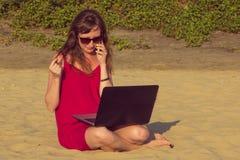Młoda kobieta w czerwieni sukni z komputerem i smartphone na bea Obraz Stock