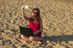 Młoda kobieta w czerwieni sukni z komputerem i smartphone na bea Obrazy Stock
