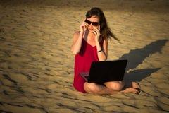 Młoda kobieta w czerwieni sukni z komputerem i smartphone na bea Fotografia Royalty Free