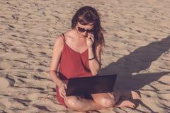 Młoda kobieta w czerwieni sukni z komputerem i smartphone na bea Zdjęcie Royalty Free