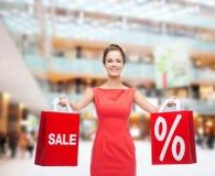 Młoda kobieta w czerwieni sukni z torba na zakupy Fotografia Stock