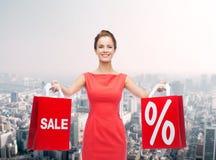 Młoda kobieta w czerwieni sukni z torba na zakupy Obrazy Stock