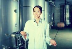 Młoda kobieta w jednolitej pozyci w wytwórnii win fermentaci Obraz Stock