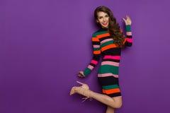 Młoda Kobieta W Kolorowej Mini sukni Stoi Na Jeden nodze Obraz Stock