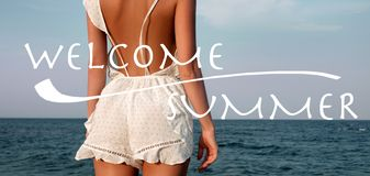 M?oda kobieta w lato sukni pozyci na pla?y i patrze? morze obrazy stock