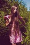 Młoda kobieta w menchiach ubiera w wysokiej zielonej trawie Obraz Royalty Free