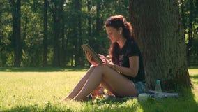 M?oda kobieta w parku u?ywa smartphone i pastylk? zbiory