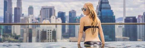 M?oda kobieta w plenerowym p?ywackim basenie z miasto widokiem w niebieskim niebie Bogaci ludzie sztandarów, DŁUGI format obrazy royalty free