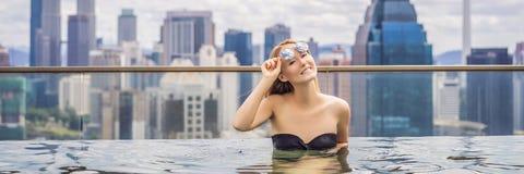 M?oda kobieta w plenerowym p?ywackim basenie z miasto widokiem w niebieskim niebie Bogaci ludzie sztandarów, DŁUGI format obraz stock