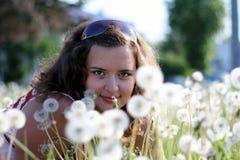 Młoda kobieta w polu z wiele dandelions Zdjęcia Stock