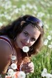 Młoda kobieta w polu z wiele dandelions Fotografia Stock