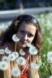 Młoda kobieta w polu z wiele dandelions Obrazy Royalty Free