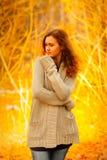 Młoda kobieta w pulowerze i cajgu stojak na jesieni tle Zdjęcie Stock