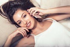 Młoda kobieta w sypialni z telefonem komórkowym w sypialni Fotografia Stock