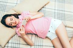 Młoda kobieta w sypialni z telefonem komórkowym w sypialni Zdjęcia Royalty Free