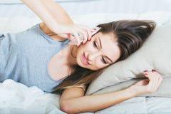 Młoda kobieta w sypialni z telefonem komórkowym w sypialni Zdjęcie Royalty Free