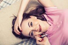 Młoda kobieta w sypialni z telefonem komórkowym w sypialni Obrazy Royalty Free
