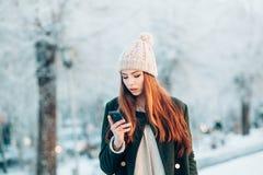 Młoda kobieta w zima parkowym opowiada telefonie komórkowym Zdjęcia Stock