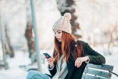 Młoda kobieta w zima parkowym opowiada telefonie komórkowym Obraz Stock