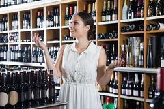 Młoda kobieta wybiera wino w dziale supermarke Zdjęcia Royalty Free