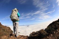 Młoda kobieta wycieczkowicz wycieczkuje na halnym szczycie Zdjęcia Stock