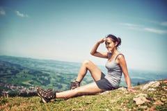 Młoda kobieta wycieczkowicza obsiadanie na grani Obraz Royalty Free