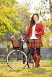 Młoda kobieta z bicyklem pozuje w parku Obraz Stock