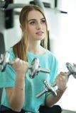 Młoda kobieta z dumbbell w gym Obraz Royalty Free