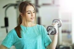 Młoda kobieta z dumbbell w gym Zdjęcie Royalty Free