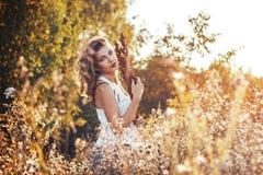 Młoda kobieta z kwiaty w jesieni polu Zdjęcia Royalty Free