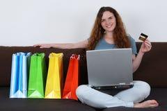 Młoda kobieta z laptopem robi interneta zakupy Fotografia Stock