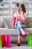 Młoda kobieta z torba na zakupy indoors stwarza ognisko domowe na kanapie Obrazy Royalty Free