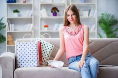 Młoda kobieta z torba na zakupy indoors stwarza ognisko domowe na kanapie Zdjęcia Stock