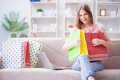 Młoda kobieta z torba na zakupy indoors stwarza ognisko domowe na kanapie Obraz Stock