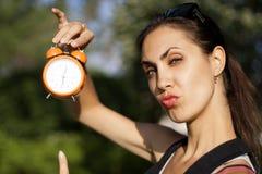 Młoda kobieta z zegarem outdoors Zdjęcia Stock