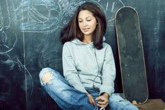M?oda ?liczna nastoletnia dziewczyna w sala lekcyjnej przy blackboard miejsca siedz?ce na sto?owy ono u?miecha si?, nowo?ytny mod zdjęcia stock