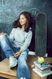 M?oda ?liczna nastoletnia dziewczyna w sala lekcyjnej przy blackboard miejsca siedz?ce na sto?owy ono u?miecha si?, nowo?ytny mod obraz stock