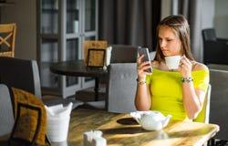 M?oda nastolatek brunetki dziewczyna z d?ugie w?osy siedz?cy salowym w miastowej kawiarni i u?ywa jej smartphone zdjęcie royalty free