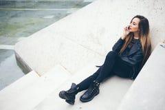 Młoda nastoletnia dziewczyna siedzi na betonowych progach i opowiada telefonem Obrazy Royalty Free