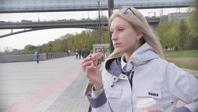 M?oda pi?kna blondynki kobieta je p?czek i cieszy si? jej smartphones podczas gdy relaksuj?cy na ?awce na rzecznym bulwarze zdjęcie wideo